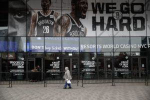 ASSOCIATED PRESS                                 A pedestrian passes an entrance to the Barclays Center in the Brooklyn borough of New York, after the NCAA's Atlantic 10 Conference Tournament was announced cancelled due to concerns over the COVID-19 coronavirus.