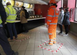 ASSOCIATED PRESS                                 People stood in marked places to keep a social distance at a fast-food restaurant in London, today. For most people, the new coronavirus causes only mild or moderate symptoms, such as fever and cough. For some, especially older adults and people with existing health problems, it can cause more severe illness, including pneumonia.