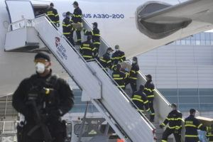 ASSOCIATED PRESS A police officer holds a weapon as firefighters unload an airplane after its arrival at the Vaclav Havel Airport in Prague on Friday. The airplane brought medical aid and protective materials against coronavirus from China.