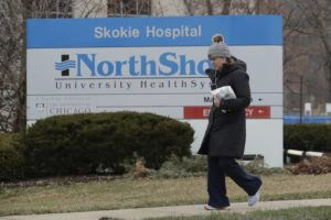 ASSOCIATED PRESS                                 A woman walks on the sidewalk in front of NorthShore Skokie Hospital sign in Skokie, Ill. Gov. J.B. Pritzker issued a stay-at-home order for the entire state, which went into effect on March 21, and lasts through at least April 7.