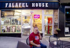 ASSOCIATED PRESS                                 Clade Karim takes a take out order over the phone for Falafel House in downtown Grandin on Monday. Karim is friends with the owner and is a self proclaimed volunteer helper for the restaurant.
