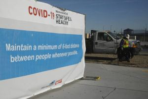 ASSOCIATED PRESS A sign gave guidelines for protection from COVID-19 as construction continued at Allegiant Stadium, future home of the Raiders NFL football team.
