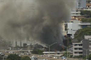 JAMM AQUINO / JAQUINO@STARADVERTISER.COM                                 Smoke billows as Honolulu firefighters work to contain a structure fire in Makiki.