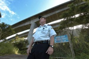 STAR-ADVERTISER / 2004 Joseph Behlert, a security guard hired by the city, stood watch on one of the roads that lead to the Haiku Stairs.