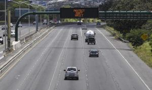 """BRUCE ASATO / BASATO@STARADVERTISER.COM                                 There were few cars on H-1 freeway near Joint Base Pearl Harbor-Hickam Sunday and a state message board that alternately tells the public to """"Protect don't infect"""" and to """"Stay home."""" Hawaii's tally of coronavirus cases rose today to 609, up two from Monday with both cases from Maui County."""