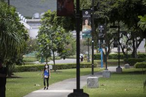 CINDY ELLEN RUSSELL / CRUSSELL@STARADVERTISER.COM                                 A solitary woman wearing a mask walks at the University of Hawaii at Manoa campus on Monday. Hawaii's tally of coronavirus cases has risen to 613, up four from Tuesday, health officials said today, with more than 84% of the patients classified as recovered.
