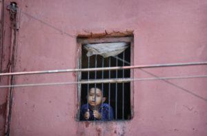ASSOCIATED PRESS A child looks out from the window of his house in the old quarters of Delhi following a lockdown amid concern over spread of coronavirus, India, March 27.