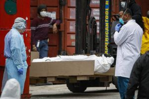 ASSOCIATED PRESS A body wrapped in plastic is prepared to be loaded onto a refrigerated container truck used as a temporary morgue by medical workers due to COVID-19 concerns, Tuesday, at Brooklyn Hospital Center in the Brooklyn borough of New York.