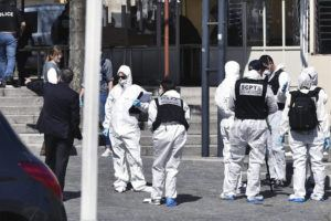 ASSOCIATED PRESS                                 Police officers investigate after a man wielding a knife attacked residents venturing out to shop in the town under lockdown in Romans-sur-Isere, southern France. The alleged attacker was arrested by police nearby, shortly after the attack. Prosecutors did not identify him. They said he had no documents but claimed to be Sudanese and to have been born in 1987.