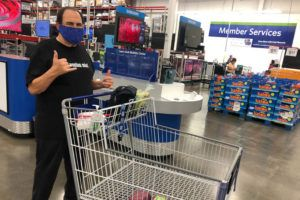 "ASSOCIATD PRESS                                 Comedian Frank De Lima poses with a ""shaka"" gesture while standing in the checkout line at a Sam's Club store in Honolulu on March 31. People in Hawaii are changing how they express aloha in the time of coronavirus. Some residents say social distancing is the antithesis of tradition in the state, where people greet each other with hugs, kisses and lei, and families are close-knit."