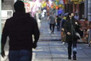 ASSOCIATED PRESS                                 A woman wearing a mask walks on Roosevelt Avenue Saturday in the Queens borough of New York.