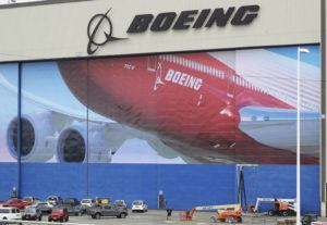 ASSOCIATED PRESS                                 A worker walks near a mural of a Boeing 747-8 airplane at the company's manufacturing facility in Everett, Wash.