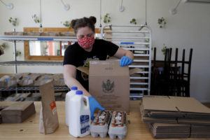 ASSOCIATED PRESS                                 Monica Mileur packs grocery items into a box at Union Loafers restaurant on April 10 in St. Louis. Some restaurants have turned to selling groceries and other provisions to customers as a way to help make up for revenue lost during the coronavirus outbreak.