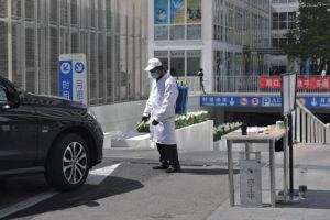 A worker wearing a protective face mask to prevent the spread of the new coronavirus sprays disinfectant as a vehicle prepares to enter to an office building carpark in Beijing.