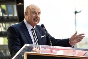 """ASSOCIATED PRESS                                 Dr. Phil McGraw speaks during a ceremony awarding him with a star on the Hollywood Walk of Fame in Los Angeles in February. Two television doctors — Dr. Oz and Dr. Phil — find themselves trying to explain comments made on Fox News Channel about the coronavirus. Dr. Mehmet Oz says he misspoke during an appearance where he said reopening schools was a """"very appetizing opportunity"""" despite the coronavirus epidemic. Meanwhile, McGraw says he used bad examples while appearing on Laura Ingraham's show when he compared coronavirus deaths to deaths caused by cigarettes, auto accidents and swimming pools."""