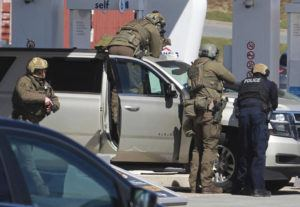 THE CANADIAN PRESS VIA AP                                 Royal Canadian Mounted Police officers surround a suspect at a gas station in Enfield, Nova Scotia.