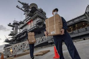 ASSOCIATED PRESS                                 Sailors assigned to the aircraft carrier USS Theodore Roosevelt move ready to eat meals for sailors who have tested negative for COVID-19 and are being taken to local hotels in an effort to implement social distancing at Naval Base Guam on April 7.