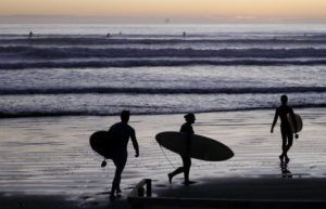 ASSOCIATED PRESS                                 Surfers prepare to enter the water at Sumner Beach as level four COVID-19 restrictions are eased in Christchurch, New Zealand, on Tuesday.