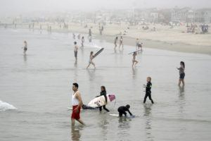 ASSOCIATED PRESS                                 Swimmers and surfers waded in the water, Sunday, in Newport Beach, Calif.