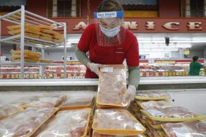 ASSOCIATED PRESS                                 Amid concerns of the spread of COVID-19, a worker restocks chicken in the meat product section at a grocery store in Dallas today.