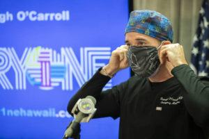 CINDY ELLEN RUSSELL / CRUSSELL@STARADVERTISER.COM                                 Dr. Darragh O'Carroll demonstrates how to put on a mask during a press conference at Honolulu Hale on Thursday.