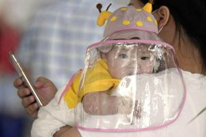 KYODO NEWS VIA AP A baby with a face shield waits to board a plane at an airport in Wuhan, central China's Hubei Province. China on Saturday reported no new confirmed cases or deaths from the new coronavirus.