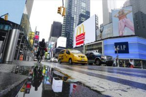 ASSOCIATED PRESS Cars and cyclists move through Times Square after a rain shower during the coronavirus pandemic.