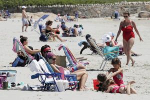 ASSOCIATED PRESS                                 Beachgoers relax on the shore at Good Harbor Beach in Gloucester, Mass., on Friday. Beaches in Gloucester reopened with restrictions after being closed two months ago due to the pandemic.