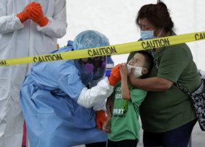 ASSOCIATED PRESS                                 Jerry A. Mann, center, is held by his grandmother, Sylvia Rubio, as he is tested for COVID-19 by the San Antonio Fire Department at a free walk-up test site in San Antonio on May 14. Public health officials have said robust testing for the coronavirus is essential to safely lifting stay-at-home orders and business closures, but states are creating confusion in the way they are reporting the data.