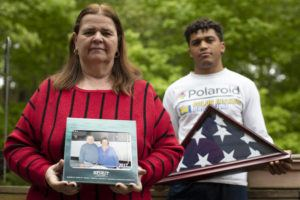 ASSOCIATED PRESS                                 Florence Hopp, left, holds a photograph of herself and her husband Robert Hopp during a cruise in 2017, as her son J.J. Brania-Hopp holds the American flag the military presented to them after his father's death at their home in Boonton, N.J. Hopp was one of at least 79 residents of a veterans home in Paramus, New Jersey, to die from COVID-19, making the state-run facility one of the nation's worst hot spots for the virus.