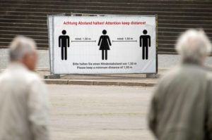 ASSOCIATED PRESS People walk in front of a poster wall displaying the distance rules at the cathedral place in Erfurt, central Germany, today. A spat is brewing between Germany's federal government and state governors over plans by some regional leaders to end pandemic-related restrictions despite fresh clusters of cases across the country.