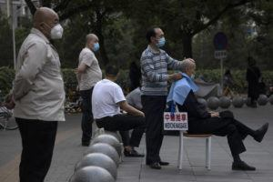 ASSOCIATED PRESS A masseur wearing a mask to curb the spread of the new coronavirus gives a customer a massage a shopping mall in Beijing today.