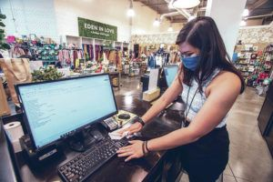 DENNIS ODA / DODA@STARADVERTISER.COM                                 Janelle Quiocho wiped and disinfected equipment at the checkout counter at Eden in Love in the South Shore Market on Tuesday. The local boutique reopened to customers on Friday.