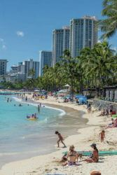 DENNIS ODA / DODA@STARADVERTISER.COM Waikiki Beach was packed Sunday after the beaches were open to the public. Multiple travelers have been arrested for breaking the 14-day quarantine rule.