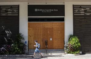 CINDY ELLEN RUSSELL / CRUSSELL@STARADVERTISER.COM                                 A mask-wearing pedestrian walks past the shuttered entrance of the Hilton Garden Inn along Kuhio Avenue in Waikiki on Monday. Hawaii's low COVID-19 infection rate has led state and county leaders to ease restrictions and gradually start reopening the economy.