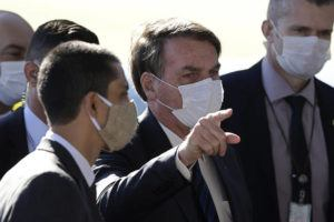 ASSOCIATED PRESS Brazil's President Jair Bolsonaro wears a face mask as he speaks to the press upon departure from the official residence of Alvorada palace in Brasilia, Brazil, on Monday.