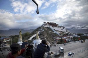 ASSOCIATED PRESS                                 Tourists took photos of the Potala Palace beneath a security camera, in Sept. 2015, in Lhasa, capital of the Tibet Autonomous Region of China. China said, Tuesday, that a boy who disappeared 25 years ago after being picked by the Dalai Lama as Tibetan Buddhism's second-highest figure is now a college graduate with a stable job.