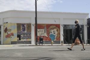 ASSOCIATED PRESS                                 A masked pedestrian walks past a coronavirus-themed mural on May 18 in the arts district of Los Angeles.