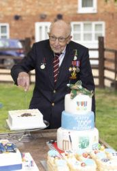 COURTESY CAPTURE THE LIGHT PHOTOGRAPHY / APRIL 30                                 Second World War veteran Captain Tom Moore cut into one of his birthday cakes as he celebrated his 100th birthday, in Bedford, England.