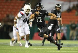 STAR-ADVERTISER / 2019                                 Hawaii quarterback Chevan Cordeiro carried the ball against the Arizona Wildcats in a 45-38 win on Aug. 24.