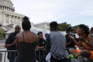 ASSOCIATED PRESS                                 U.S. Capitol police officers talk with demonstrators as they have a conversation about racism in America as they protest the death of George Floyd, Wednesday on Capitol Hill in Washington.