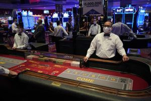 ASSOCIATED PRESS                                 Dealers in masks wait for customers before the reopening of the D Las Vegas hotel and casino Wednesday in Las Vegas. Casinos were allowed to reopen today after temporary closures as a precaution against the coronavirus.
