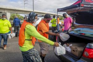 DENNIS ODA / DODA@STARADVERTISER.COM                                 Brian Mendoza and Leon Barber load food items into cars during the Show Aloha Challenge food distribution at the Aloha Stadium parking lot on Tuesday morning. Hawaii's closure of tourism to fight the spread of COVID-19 has flattened the state's economy, leaving tens of thousands of residents in need of food assistance.
