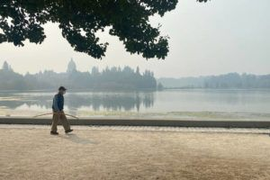 ASSOCIATED PRESS                                 A man wearing a mask walked by the lake outside of the Washington State Capitol in Olympia, Wash., today. Olympia is among the places facing unhealthy air quality due to wildfires in the Pacific Northwest.