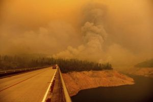 ASSOCIATED PRESS                                 A plume rises from the Bear Fire as it burns along Lake Oroville on Wednesday in Butte County, Calif.