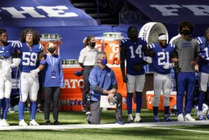 ASSOCIATED PRESS                                 Indianapolis Colts head coach Frank Reich takes a knee during the national anthem before an NFL football game against the Minnesota Vikings today in Indianapolis.