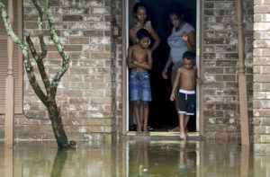 GODOFREDO A. VáSQUEZ/HOUSTON CHRONICLE VIA ASSOCIATED PRESS                                 Eight-year-old Cam'ron Maltie, left, and Adrian Murray, 4, looked at their flooded front lawn during Tropical Storm Beta, today, in Houston. Their family has been living in the home for a year and didn't know the neighborhood flooded.