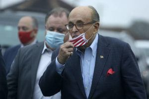 ASSOCIATED PRESS                                 Former New York Mayor Rudy Giuliani lowers his face mask as he approaches supporters, Monday, during a Columbus Day gathering at a Trump campaign field office in Philadelphia.