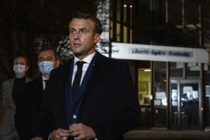ASSOCIATED PRESS                                 French President Emmanuel Macron, flanked by French Interior Minister Gerald Darmanin, second left, speaks in front of a high school Friday in Conflans Sainte-Honorine, northwest of Paris, after a history teacher who opened a discussion with high school students on caricatures of Islam's Prophet Muhammad was beheaded.