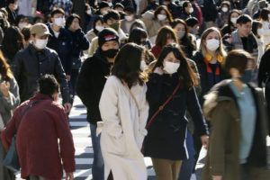 KYODO NEWS VIA AP                                 People wearing face masks to help curb the spread of the coronavirus walk around the scrambled intersection at the Shibuya shopping district in Tokyo. Tokyo has confirmed 949 new cases of the coronavirus on Saturday, a record high for the Japanese capital, as the country struggles with an upsurge that is spreading nationwide.